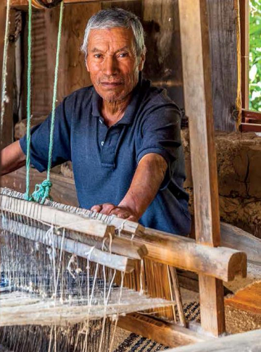 Weaver Demetrio Ramos with the loom he has been weaving on his whole life. Photo by Joe Coca.