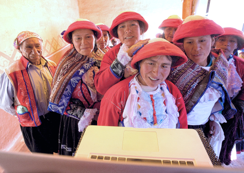 Weavers in Peru marvel at seeing themselves on a computer monitor. Photo by Joe Coca.