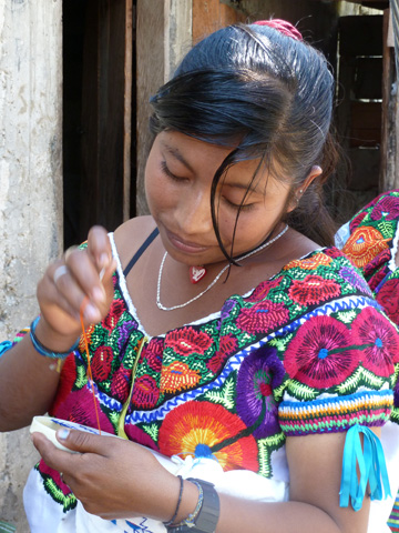 Tzeltal weekend: A young girl in the hamlet of Sibaca wears a huipil with cross- stitched yoke and a wide border of satin-stitched flowers.