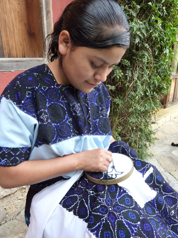 A young girl from San Andres works cross stitch in the local style.