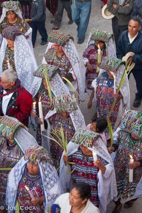 The striking Maya huipils, cortes, and shawls of Nebaj are softened by Catholic veils.
